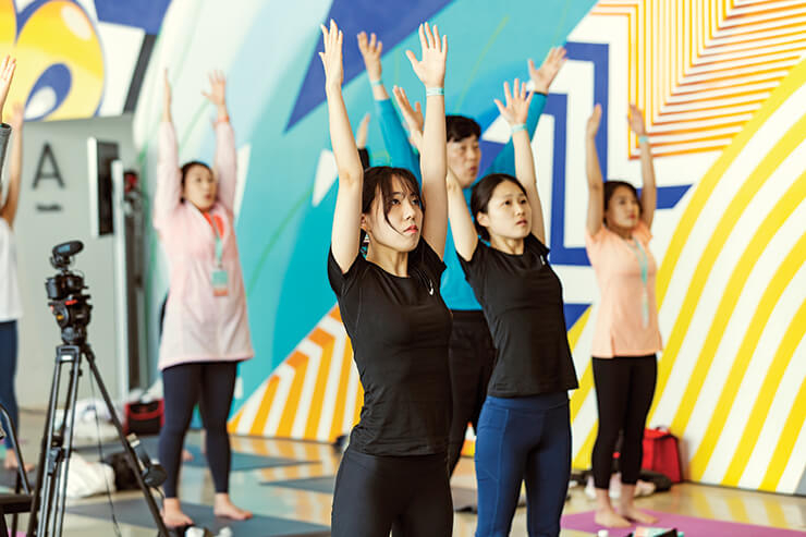 참가자들이 강하나 강사의 스트레칭 동작을 보며 열심히 따라 하고 있다.