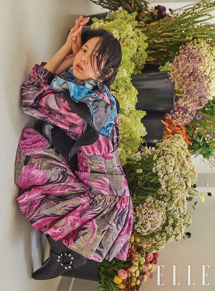 대담한 플라워 프린트와 러플 디테일이 돋보이는 미니드레스, 블랙 앵클부츠는 가격 미정, Louis Vuitton.