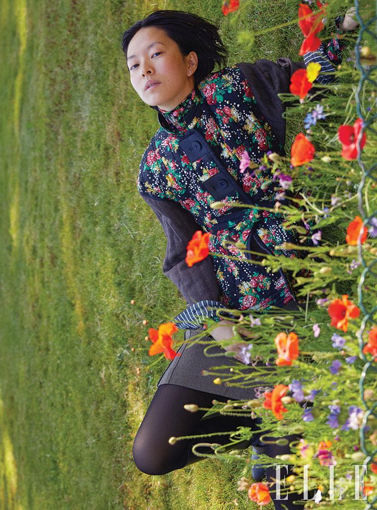 잔잔한 플라워 프린트와 반짝이는 크리스털 장식의 벨티드 재킷, 플라워 프린트 터틀넥, 심플한 미니스커트는 가격 미정, 모두 Louis Vuitton.