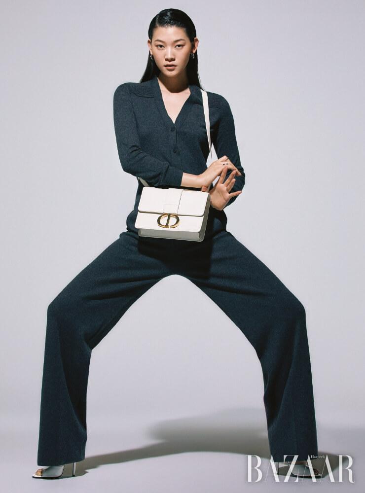 니트 소재의 점프수트는 Loro Piana, 이니셜 장식 가방은 Dior, 귀고리는 5만8천원 S_S.il, 검지에 낀 반지는 12만8천원 Monica Vinader, 약지에 낀 반지는 Hermès, 오픈 토 뮬은 81만원 Gucci.