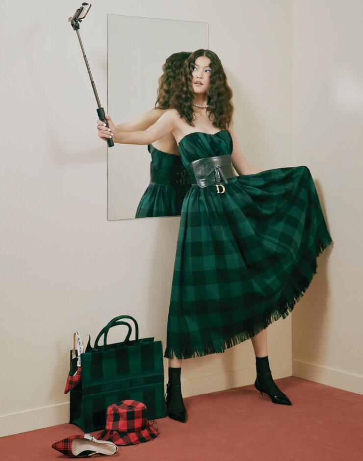 튜브톱 드레스, 진주 초커, 반지, 벨트, 삭스, 슈즈, 바닥에 놓인 쇼퍼 백, 모자, 슬링백 슈즈는 모두 Dior.