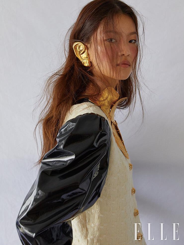 페이턴트 소재를 믹스한 빈티지한 원피스와 귀 모양의 귀고리, 볼드한 목걸이는 모두 Gucci.