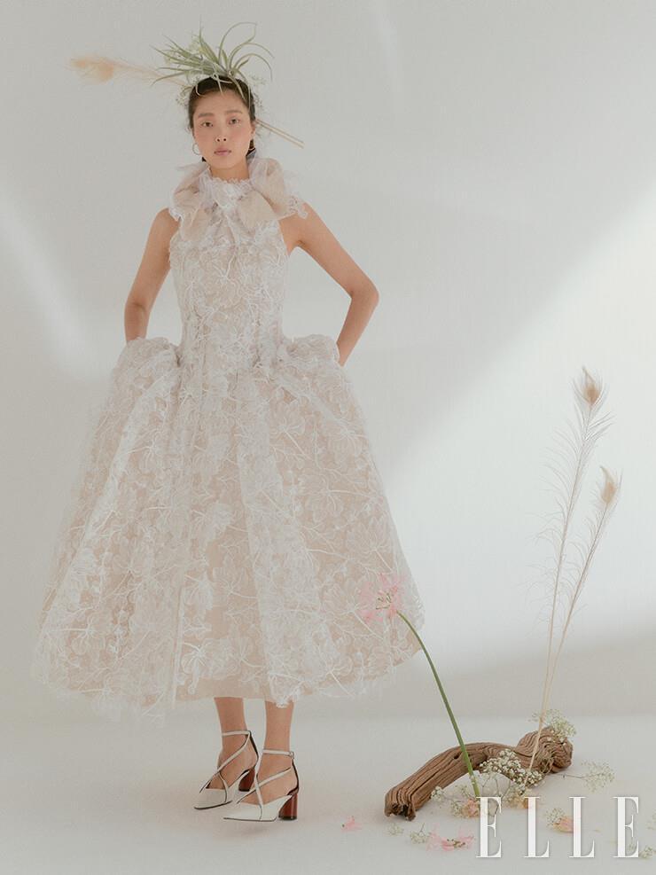 네크라인의 러플과 전체적인 볼륨감이 돋보이는 드레스는 Maticevski by Beyond the Dress. 이어링은 Dior Fine Jewelry. 슈즈는 Rachel Cox.