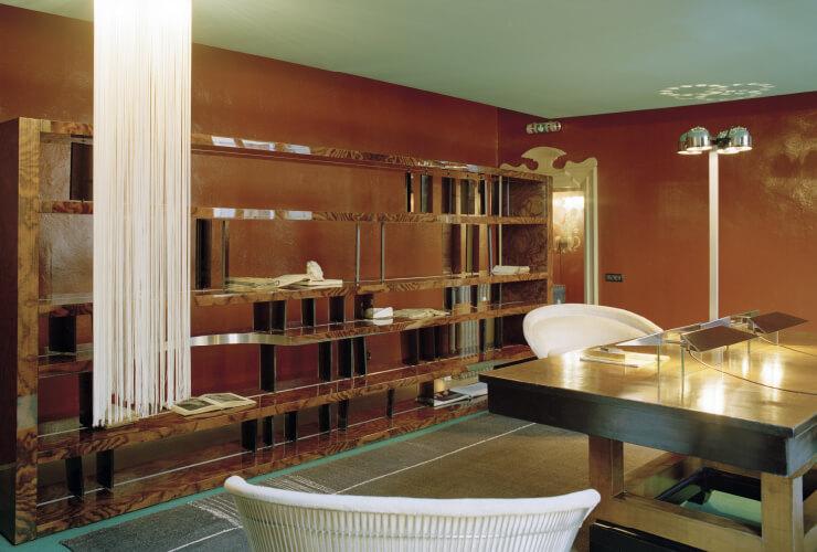 디모레 갤러리의 한 공간. 뿌리목과 스모크 글라스(연기를 쐬어 어둡게 만든 유리)로 이루어진 선반은 디모레 스튜디오가 디자인했다. 선반 앞에 가늘고 길게 늘어진 1970년대 샹들리에는 현대미술가 마리요 야지와 스튜디오 사이먼의 협업 작품. 1920년대 흑단색 테이블은 건축가 피에로 포르탈루피의 디자인. 1960년대 암체어는 모더니즘의 아이콘 워런 플래트너의 디자인. 1970년대 플로어 램프는 가에 아울렌티의 디자인.