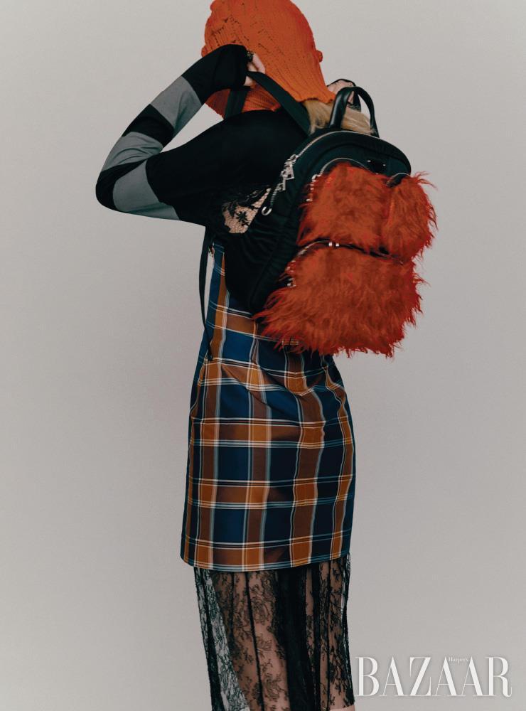 드레스는 3백31만원, 레이스 브라는 가격 미정, 백팩은 2백21만원 모두 Prada. 레이어드한 체크 스커트는 54만8천원 Push Button. 니트 발라클라바는 54만원 4 Moncler Simone Rocha. 버킷 모자는 Dior. 양손에 착용한 반지들은 모두 Louis Vuitton.