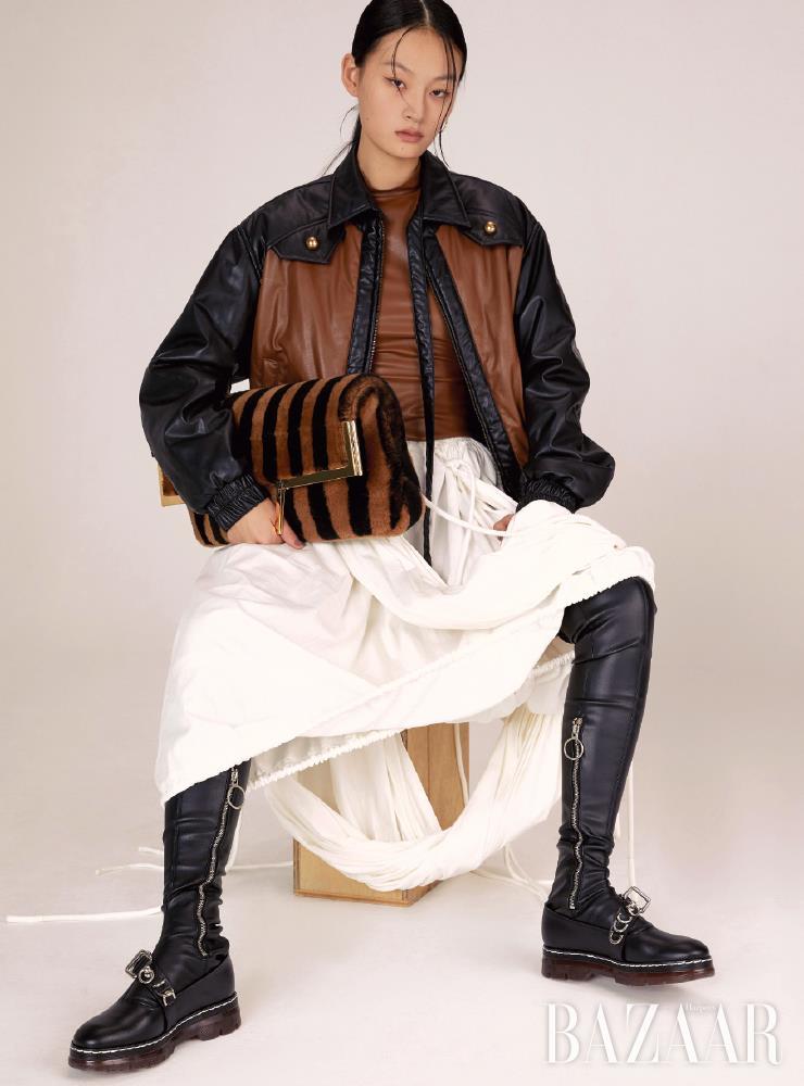 재킷은 70만원, 톱은 32만원, 스커트는 50만원 모두 Kijun. 귀고리는 38만원 Beauton. 하이 삭스는 33만원, 로퍼는 69만원 모두 Cédric Charlier. 스트라이프 패턴의 시어링 쇼퍼 백은 가격 미정 Fendi.