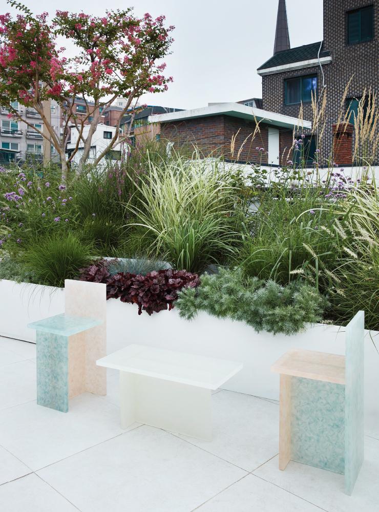 한국의 자생식물을 연구하며 가든 문화를 만들어가는 플로시스(Flosys)가 디자인한 옥상정원, 염색한 한지와 레진으로 몽환적인 가구를 만드는 손상우 작가의 'Kiri' 체어와 테이블이 놓여 있다. 사진/ 신채영