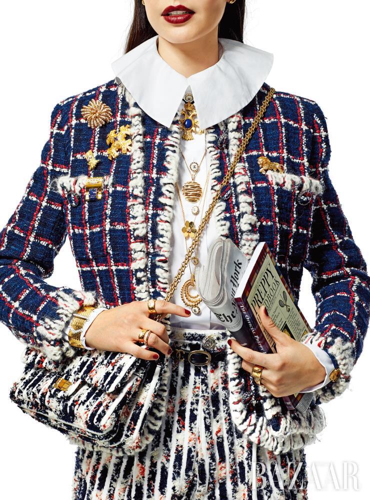재킷, 블라우스, 팬츠, 벨트, 백은 모두 Chanel. 귀고리는 Chanel Fine Jewelry. 맨 위 독수리 펜던트 목걸이는 Van Cleef & Arpels by FD Gallery. 두 번째와 네 번째 목걸이는 모두 David Yurman. 꽃 펜던트 목걸이, 왼쪽 맨 위에 장식한 클립, 왼쪽 주머니에 장식된 클립, 팔찌, 시계는 모두 Van Cleef & Arpels. 십자 모티프 브로치는 Tiffany & Co. by Beladora Vintage. 나무 브로치는 Cartier by Beladora Vintage. 사자 브로치는 Chanel Fine Jewelry. 오른손 약지 위쪽에 낀 반지는 De Beers. 나머지 반지는 모두 Chanel Fine Jewelry.