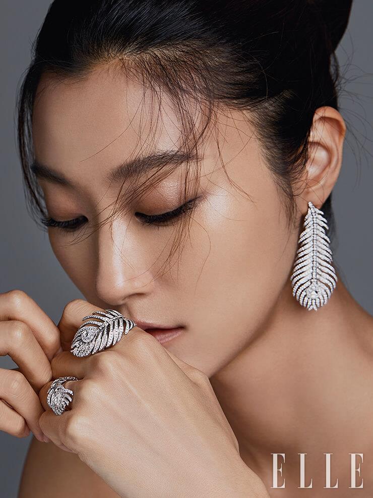 공작 깃털을 모티프로 한 이어링은 가격 미정, 검지에 착용한 0.51캐럿의 다이아몬드를 중심으로 314개의 다이아몬드가 세팅된 링은 6천만원대, 약지에 착용한 1개의 다이아몬드를 중심으로 142개의 다이아몬드가 세팅된 링은 1천만원대, 모두 Boucheron.