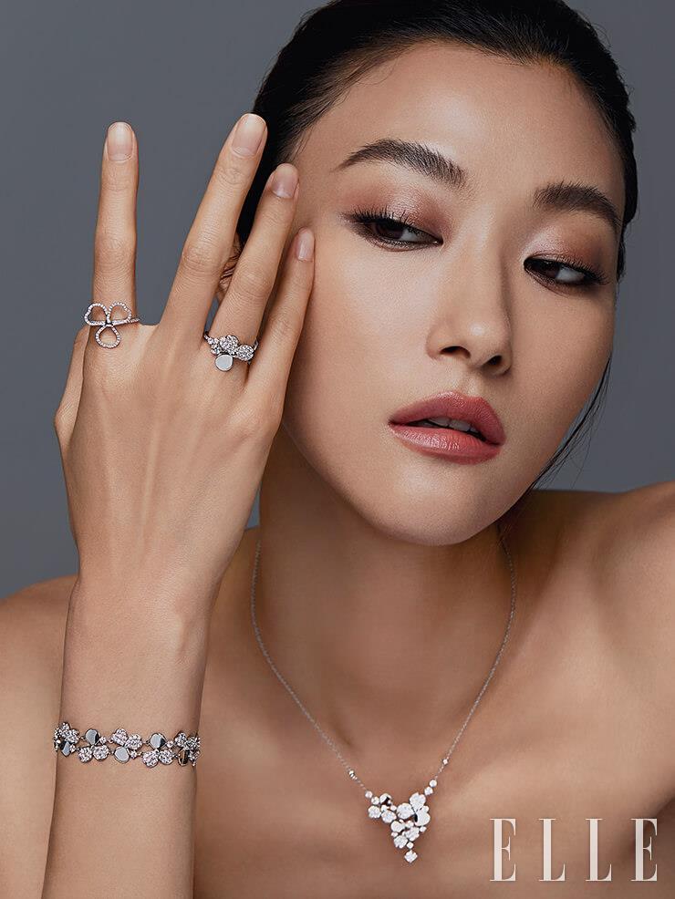 플라워 모티프로 다이아몬드가 세팅된 티파니 페이퍼플라워 컬렉션 네크리스와 검지에 착용한 플래티넘 위에 라운드 브릴리언트 다이아몬드가 세팅된 오픈 플라워 링, 약지에 착용한 플라워 링, 비대칭을 이루는 꽃잎들이 돋보이는 브레이슬렛은 모두 가격 미정, Tiffany & Co.
