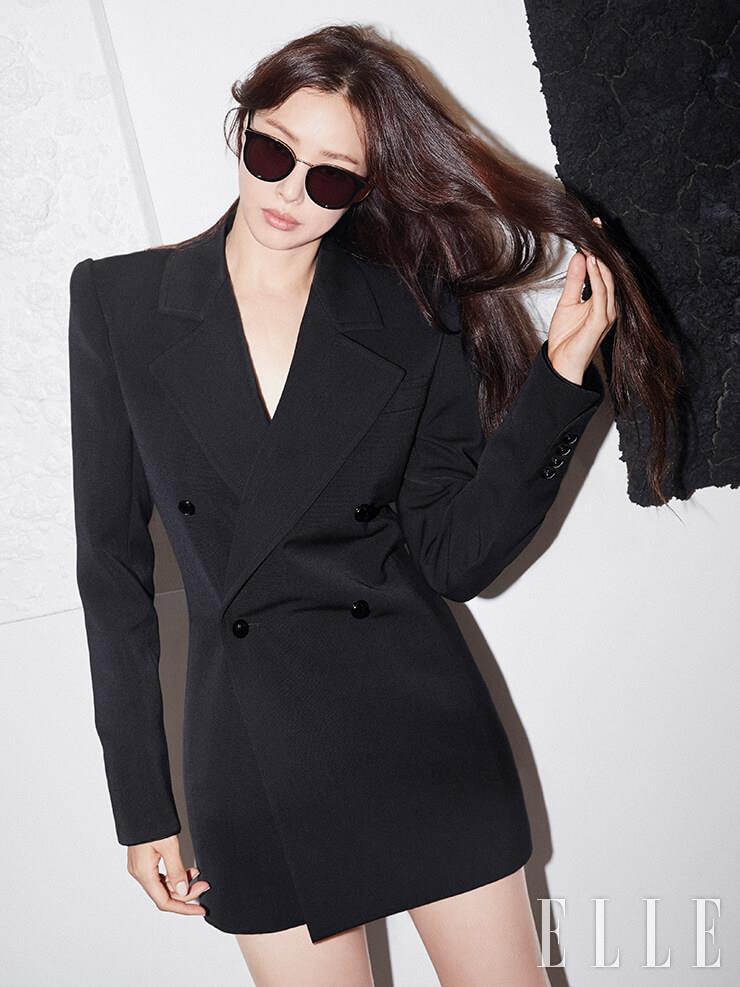 블랙 앤 골드 프레임으로 시크한 무드를 연출하는 선글라스는 DKNY. 와이드 숄더 재킷은 Saint Laurent by Anthony Vaccarello.