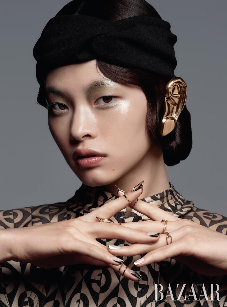 귀를 덮는 액세서리, 로고 패턴 코트는 모두 Gucci. 네일 주얼리는 Unistella. 터번 헤어밴드는 스타일리스트 소장품.