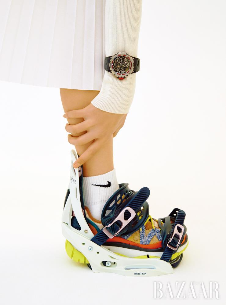 블랙 러버 스트랩의 '엑스칼리버 스파이더 스켈레톤 더블 플라잉 투르비옹' 시계는 3억6천6백50만원 Roger Dubuis. 니트 톱은 가격 미정 SportMax. 플리츠 스커트는 1백45만원 Sacai. 양말은 1만6천원 Nike. 스니커즈는 가격 미정 Chloe. 스노보드 바인딩은 45만1천원 Burton.