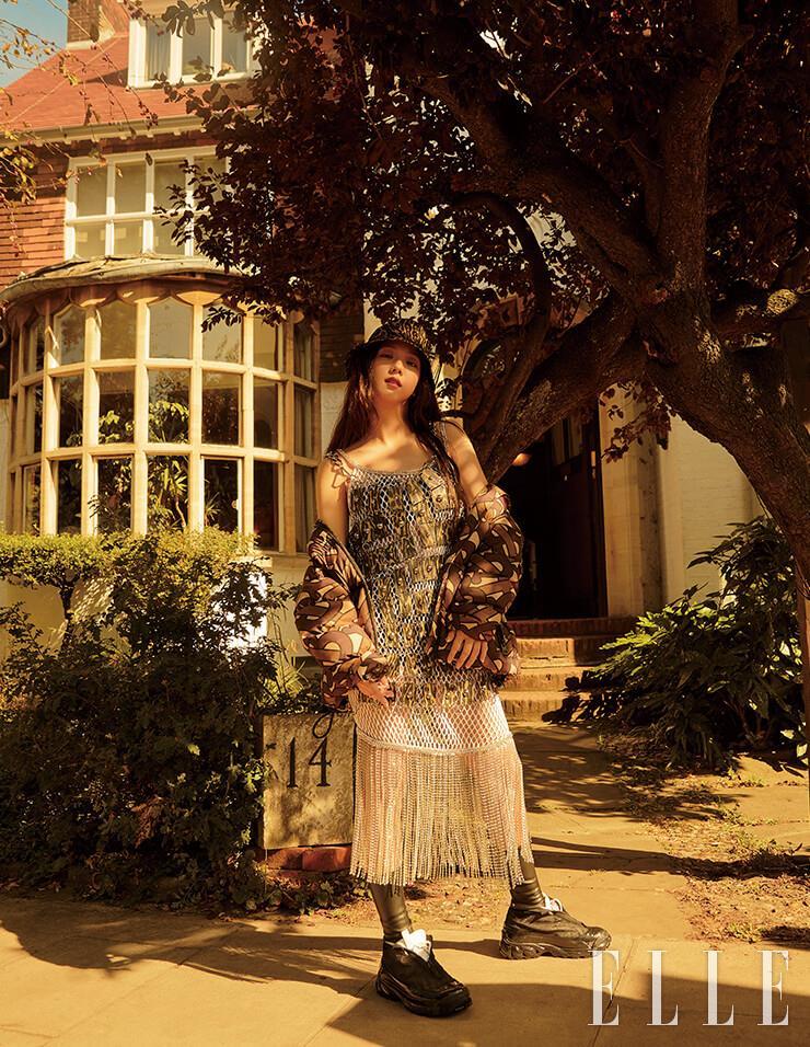 모노그램 프린트의 패딩 재킷과 크리스털 프린지 장식의 네트 드레스, 블랙 톱, 레오퍼드 프린트 레더와 체인 장식 드레스, 버킷 햇, 블랙 스니커즈는 모두 Burberry.