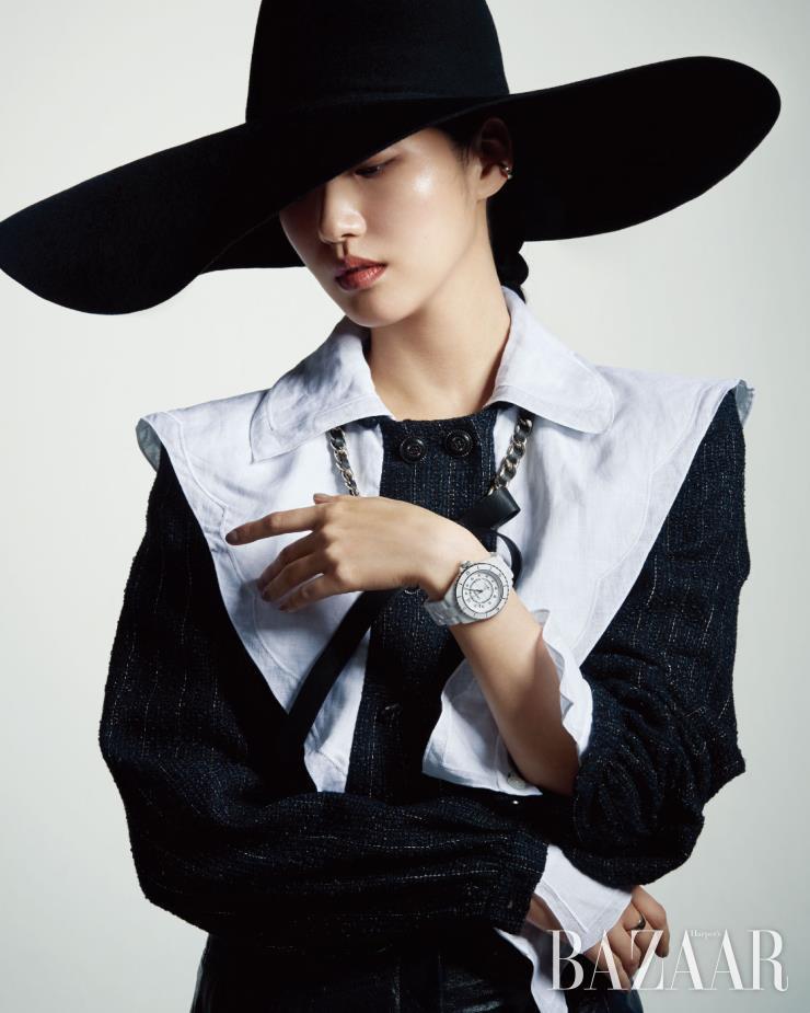 퀼팅 디테일의 '코코 크러쉬' 이어커프, 다이아몬드 인디케이터가 장식된 세라믹 소재의 'J12 화이트' 워치, 오른손 중지에 낀 베이지 골드 '코코 크러쉬' 스몰 링은 모두 Chanel Watch & Fine Jewelry. 모자는 Shinjeo.