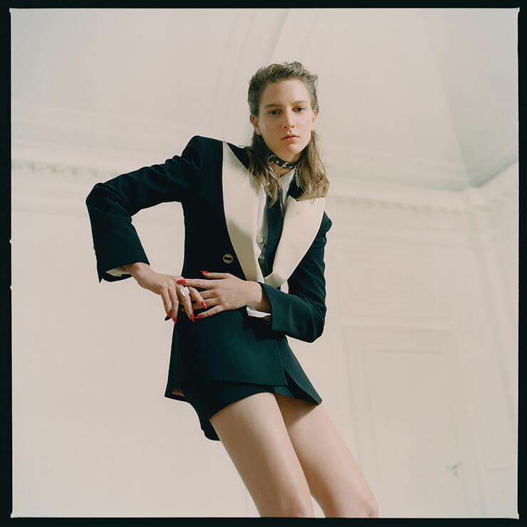 피크트 라펠 재킷은 2650파운드, 스커트는 620파운드, 셔츠는 520파운드, 블랙 타이는 145파운드, 모두 Gucci. 초커는 55파운드, Underground. 스퀘어 링은 165파운드, Vivienne Westwood.
