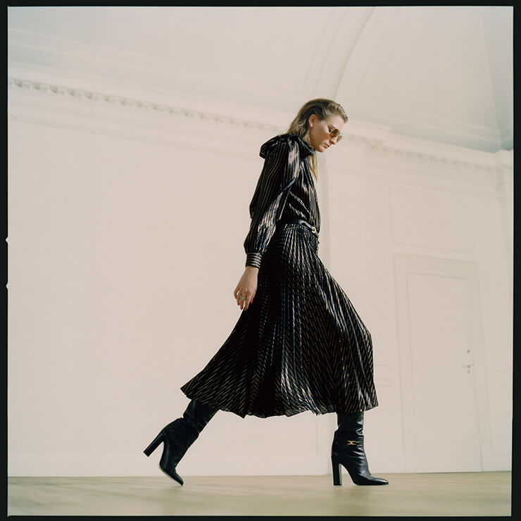 리본 장식의 핀스트라이프 드레스는 5900파운드, 레더 롱부츠는 1400파운드, 선글라스는 290파운드, 모두 Celine by Hedi Slimane. 링은 165파운드, Vivienne Westwood.