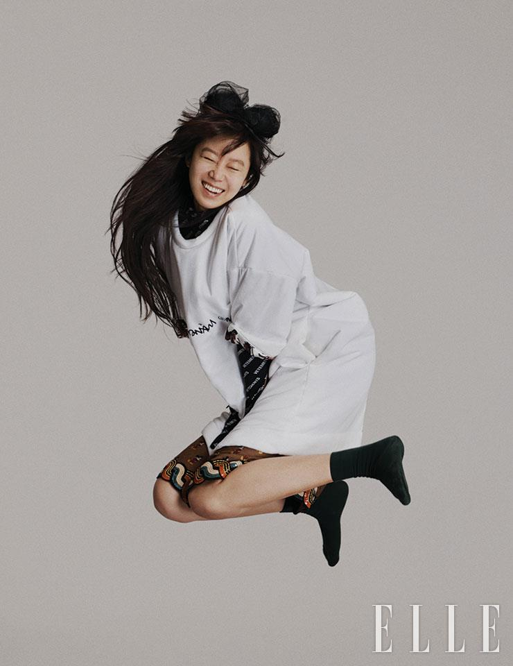 오버사이즈 화이트 티셔츠는 MM6. 로고 플레이 톱은 Vetements. 미키 마우스 패턴의 스커트는 Gucci. 헤어밴드는 Maison Michel. 양말은 스타일리스트 소장품.