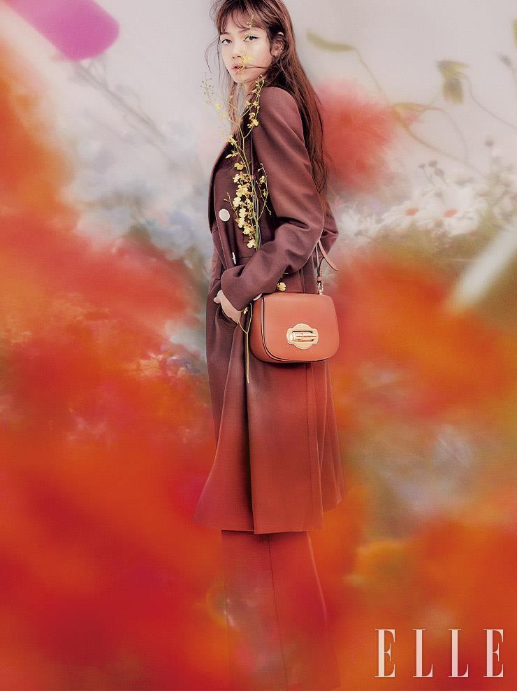브라운 컬러 스프링 맥시 코트와 팬츠, 골드 버클 장식 트위스트 클로저 숄더백은 모두 Prada.