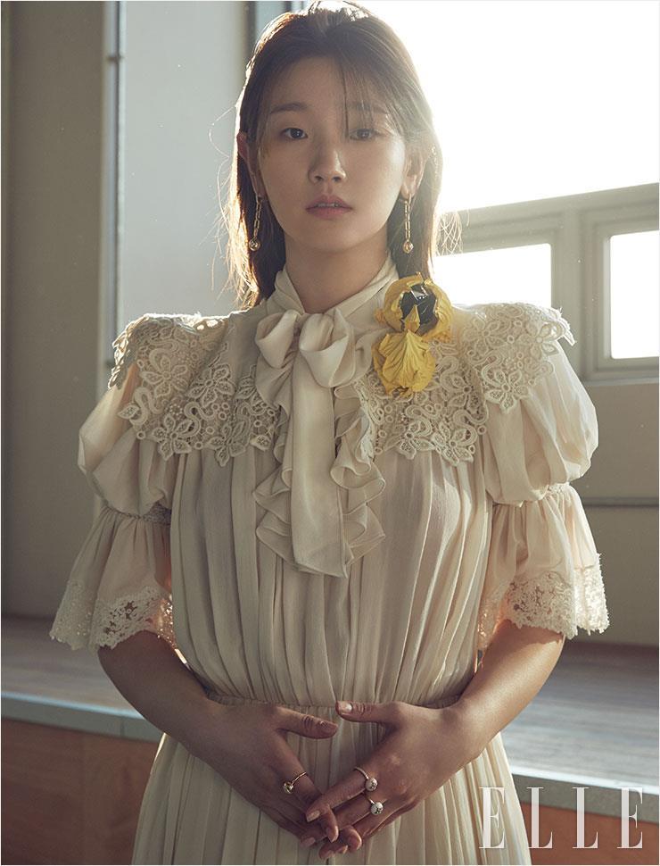 레이스와 셔링 장식의 드레스, B 블라썸 파인 주얼리 링과 이어링은 모두 Louis Vuitton.