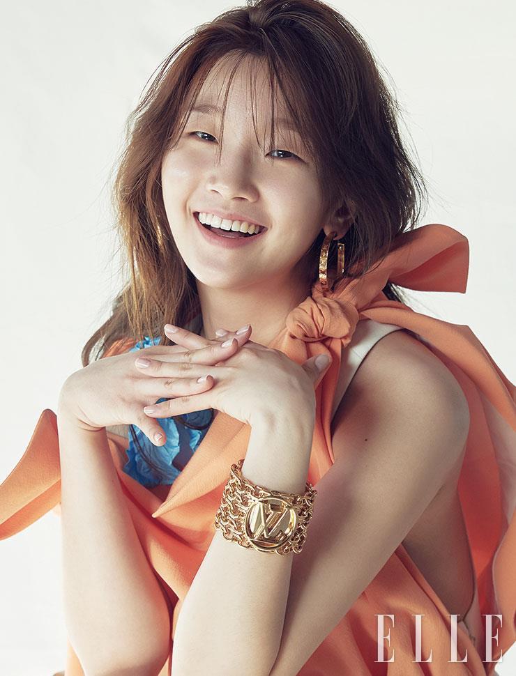오렌지와 화이트 컬러 블록의 미니드레스, 로고 장식의 브레이슬렛과 후프 이어링은 모두 Louis Vuitton.