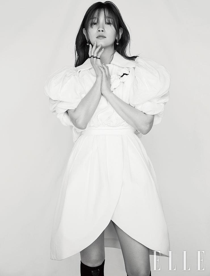 어깨를 강조한 화이트 드레스, B 블라썸 파인 주얼리 이어링, 4개가 한 세트인 모노그램 패턴의 링, 롱부츠는 모두 Louis Vuitton.