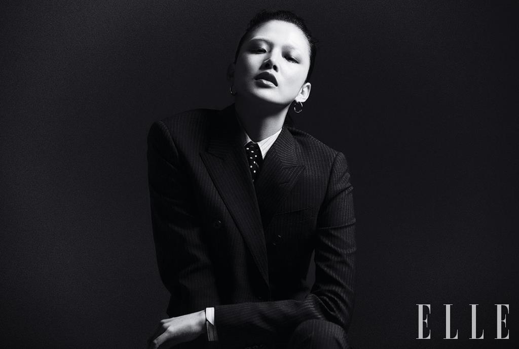 핀스트라이프 테일러드 재킷과 팬츠, 셔츠, 도트 프린트의 타이는 가격 미정, 모두 Celine by Hedi Slimane. 미니멀한 후프 이어링은 가격 미정, Givenchy.