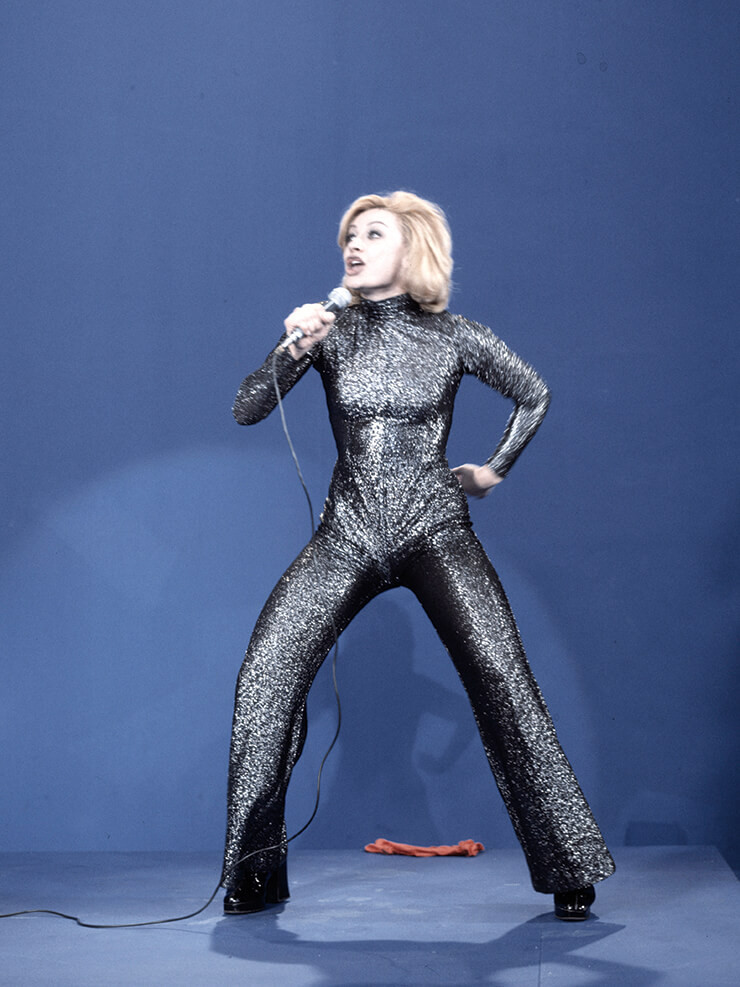 1975년 이탈리아의 배우이자 가수인 라펠라 카라(Raffella Carra`)가 점프수트를 입고 노래를 부르고 있다.