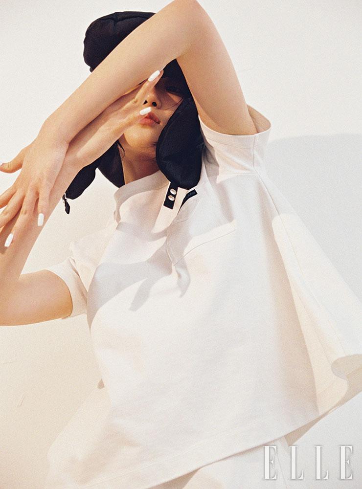 심플한 화이트 티셔츠와 플레어스커트, 패딩 트래퍼 햇은 가격 미정, 모두 Prada.