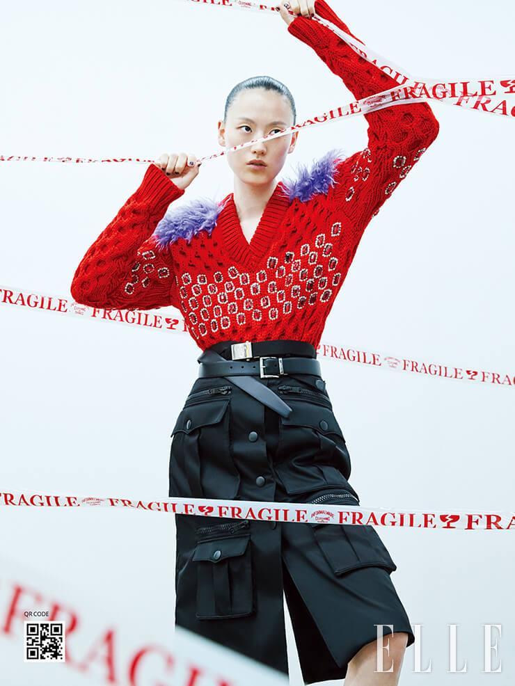 퍼와 주얼 장식이 인상적인 스웨터와 포켓 스커트, 더블 벨트, 볼드한 아웃솔의 로퍼는 가격 미정, 모두 Prada.