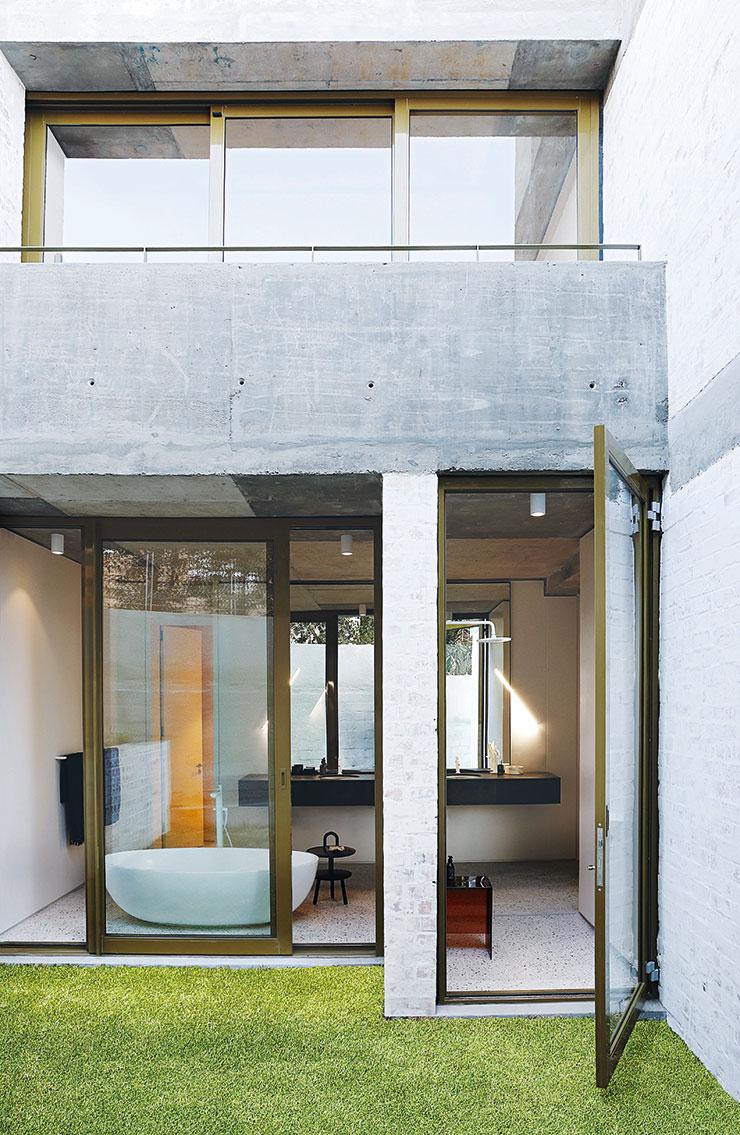 유리벽 너머로 보이는 타원형 욕조는 Still Bathrooms.