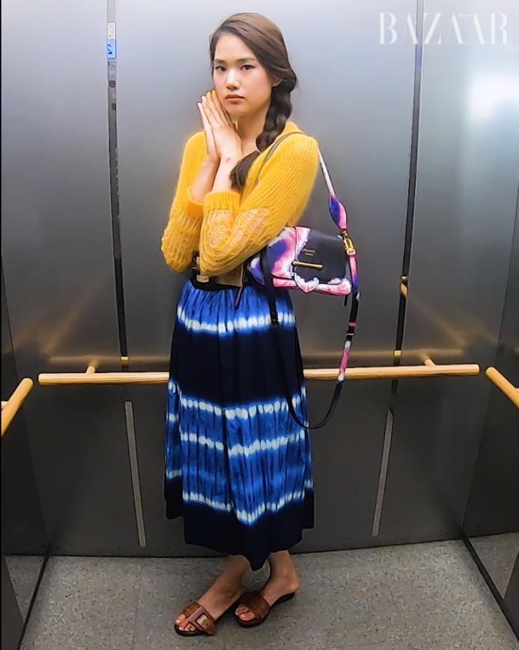 카디건은  N˚21, 타이다이 스커트는  Zara, 벨트는  Staud by Net-A-Porter, 타이다이 백은  Prada, 슬라이드는  Chloe 제품 .