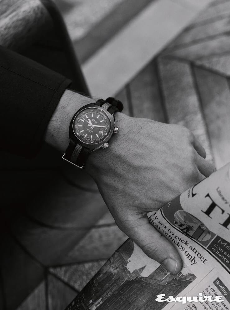 ORIS 크로노리스 데이트, 39mm 스테인리스스틸, 회색 나토 스트랩, 185만원. 남색 재킷 윌리엄 앤 선.