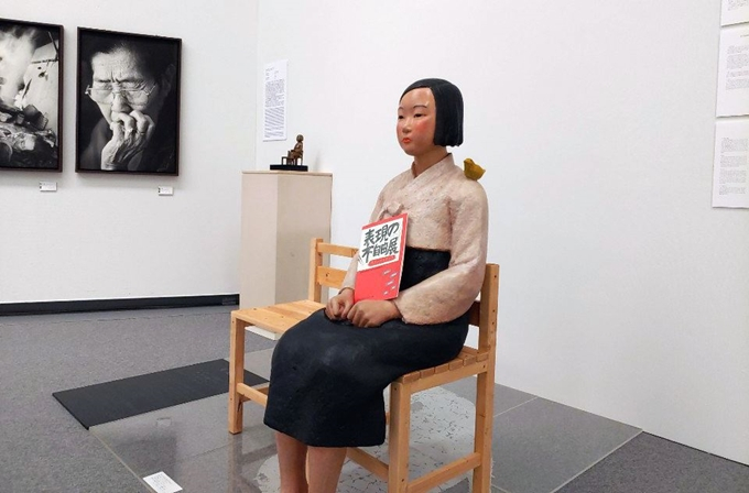 손에 '표현의 부자유전' 팸플릿이 들려있는 '평화의 소녀상'.