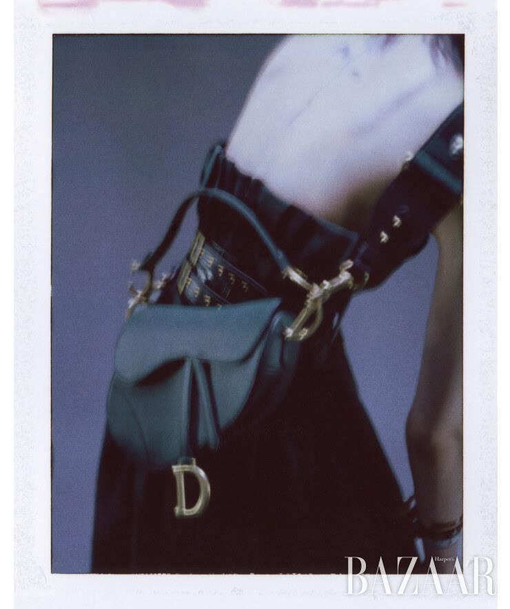 울 뷔스티에 점프수트, 체크 스커트, 엠브로이더리 스트랩 장식 새들 백, 벨트, 오른팔에 착용한 스트랩 팔찌는 모두 Dior.