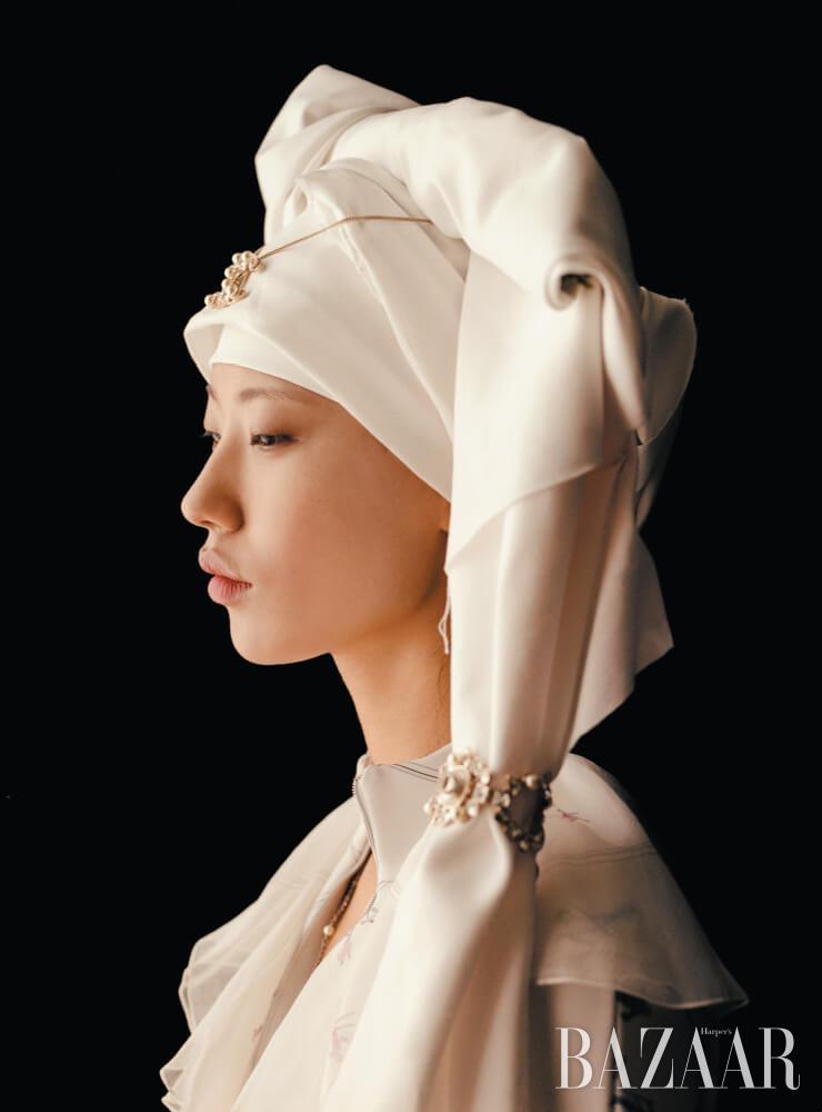 보디수트, 시어한 드레스, 목걸이, 헤어 피스에 착용한 로고 목걸이, 팔찌는 모두 Chanel.