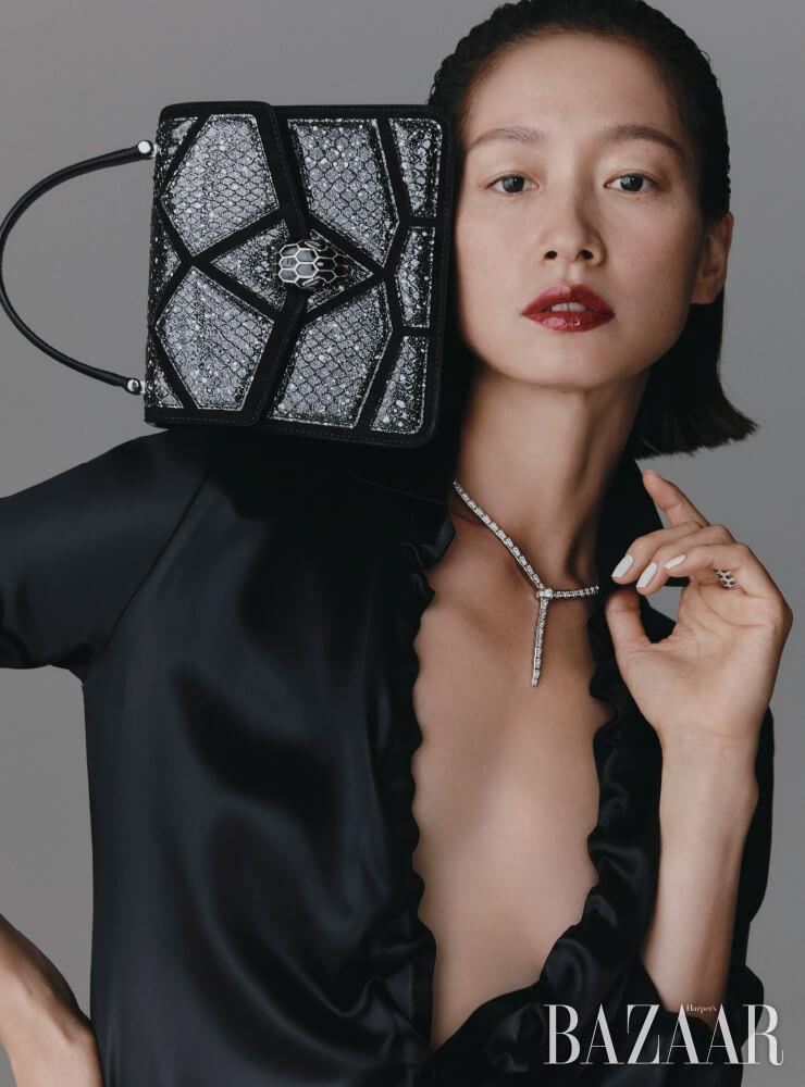 화이트 골드에 다이아몬드가 세팅된 '세르펜티' 목걸이와 반지, 스타더스트 모티프의 블랙 카프 레더 소재에 뱀 머리 클로저를 더한 파이톤 레더 '세르펜티 포에버' 백은 모두 가격 미정 Bvlgari. 새틴 셔츠는 Bottega Veneta.