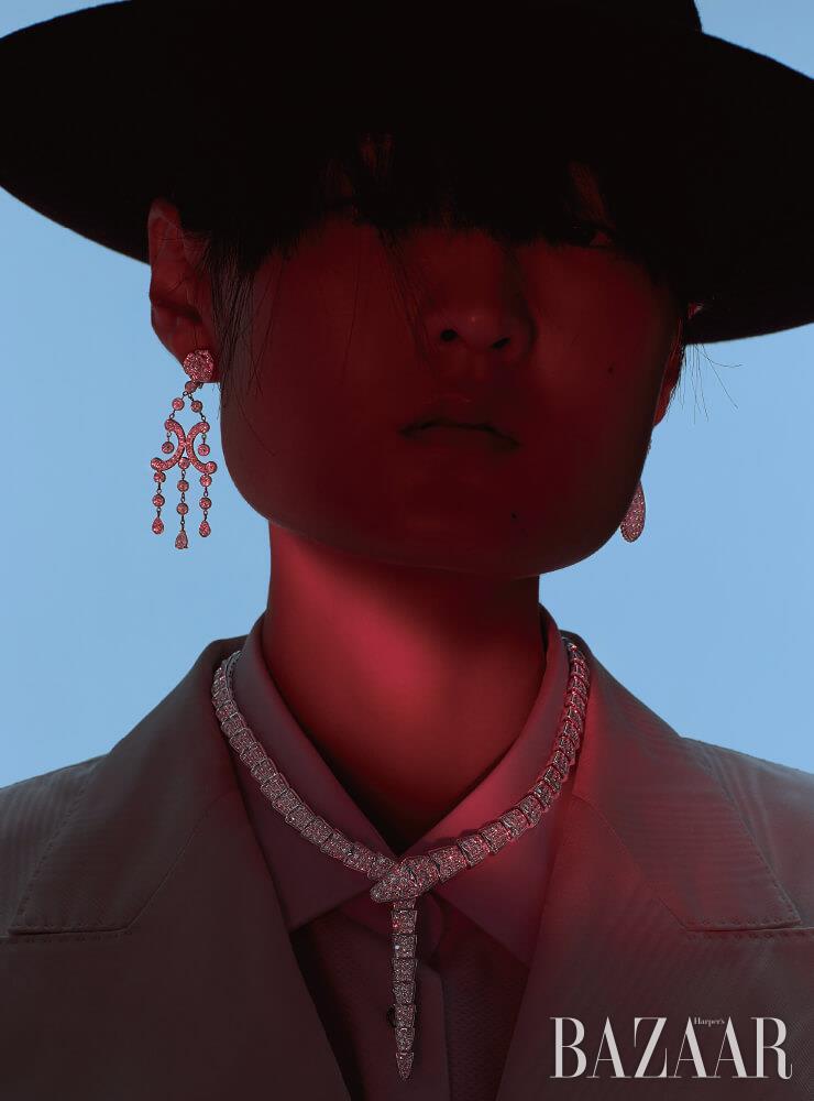 오른쪽 귀에 착용한 화이트 골드에 다이아몬드가 세팅된 '로즈' 귀고리는 Piaget. 왼쪽 귀에 착용한 뱀 머리 모티프의 '쎄뻥 보헴 드롭' 귀고리는 5천만원대 Boucheron. 화이트 골드에 다이아몬드가 장식된 '세르펜티' 목걸이는 1억3천7백만원대 Bvlgari. 재킷, 셔츠, 페도라는 모두 Dolce & Gabbana.