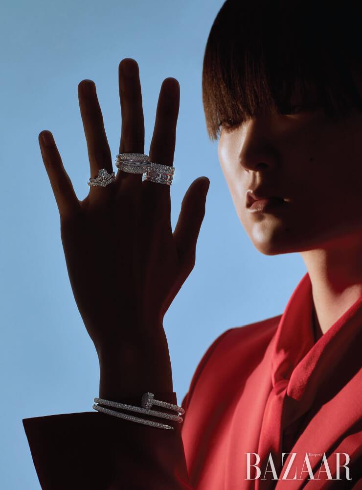 약지에 착용한 플래티넘 소재에 다이아몬드가 세팅된 '조세핀 스플렌도르 임페리얼 솔리테어' 반지는 Chaumet. 중지에 착용한 화이트 골드에 다이아몬드가 세팅된 '석세스' 반지는 Fred. 검지에 착용한 화이트 골드에 다이아몬드가 세팅된 '콰트로 레디언트' 반지는 1천만원대 Boucheron. 화이트 골드에 다이아몬드가 세팅된 '저스트 앵 끌루 더블' 팔찌는 Cartier. 재킷, 블라우스는 모두 Hugo Boss.
