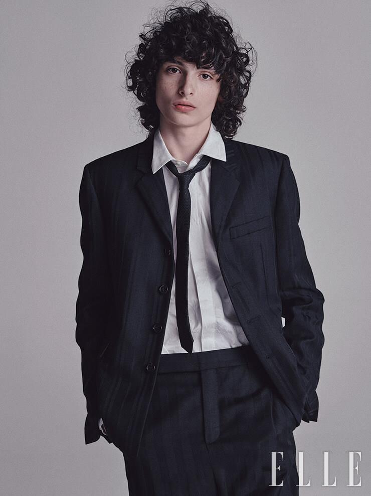 울 소재의 스트라이프 재킷과 팬츠, 화이트 셔츠, 블랙 타이는 모두 Saint Laurent by Anthony Vaccarello.