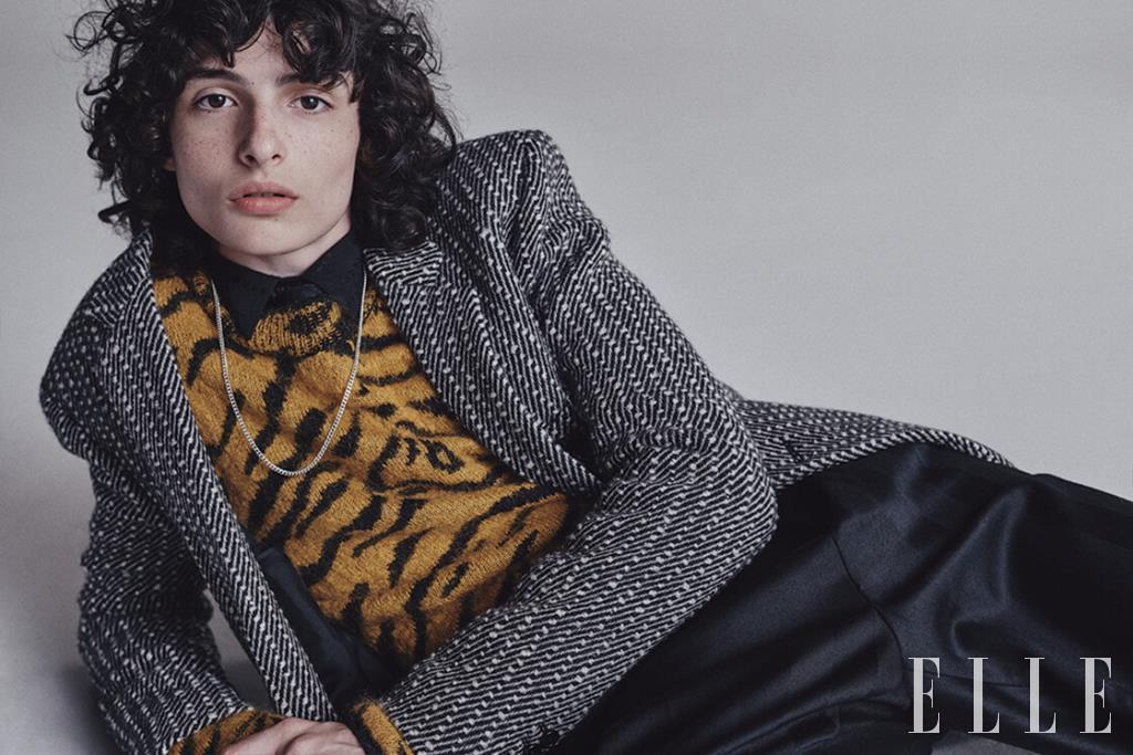 헤링본 재킷과 지브라 패턴의 풀오버, 블랙 셔츠와 타이, 팬츠는 모두 Saint Laurent by Anthony Vaccarello.