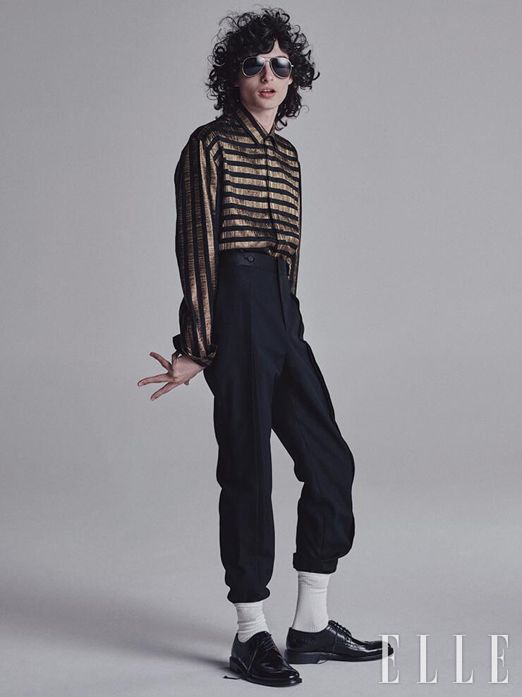 골드 스트라이프 셔츠와 더블 버튼 턱시도 팬츠, 더비 슈즈, 보잉 선글라스는 모두 Saint Laurent by Anthony Vaccarello.