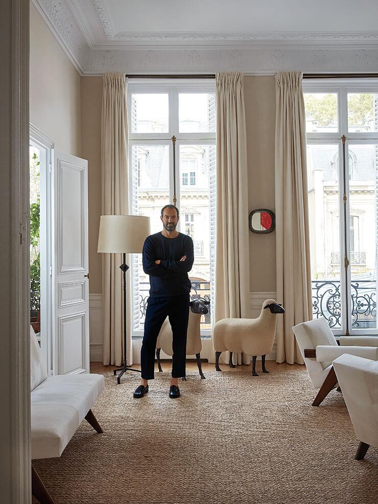 집주인 엠마누엘 드베제가 가장 좋아하는 소품 중 하나인 프랑수아-자비에 랄란(François-Xavier Lalanne)의 양 조각상 옆에 서 있다. 플로어 램프는 알베르토 자코메티의 빈티지 제품.