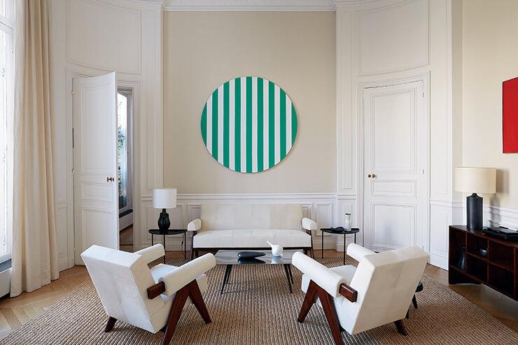 거실에 놓인 키 낮은 암체어와 소파는 피에르 잔느레가 인도 찬디가르 프로젝트를 위해 디자인한 가구 컬렉션이다. 세로 스트라이프가 돋보이는 원형 미술품은 프랑스 아티스트 다니엘 뷔랑의 작품. 커피 테이블은 론 아라드가 디자인했다.