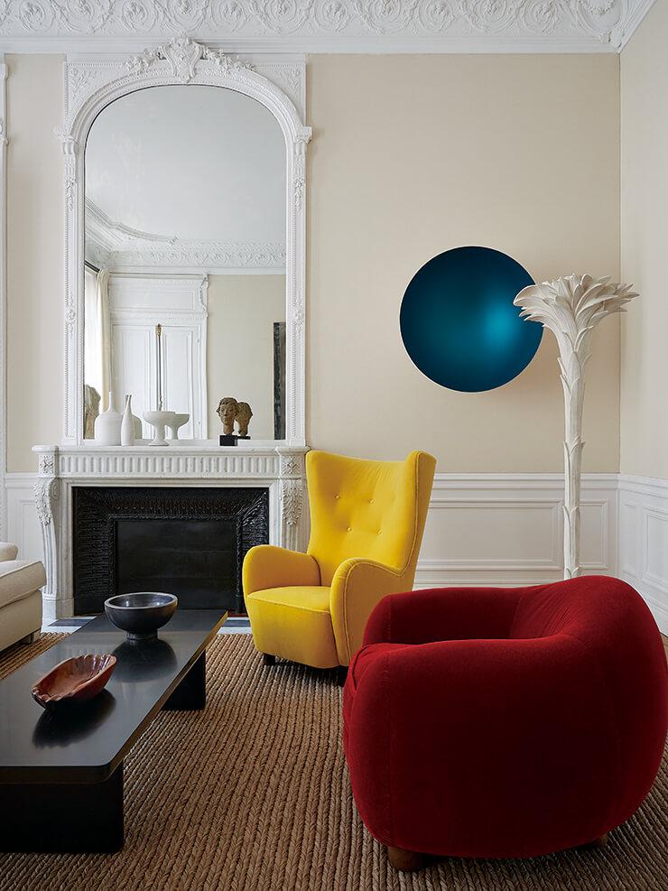 옐로 컬러의 암체어는 덴마크 인테리어 브랜드 바이 라센(By Lassen)에서 구입한 것. 레드 컬러의 '우르스 폴레르' 체어는 장 루아예르의 빈티지 아이템이다. 석고 소재의 플로어 조명은 세르주 로슈 제품. 벽면에 설치된 미술품은 아니시 카푸어의 작품이다.