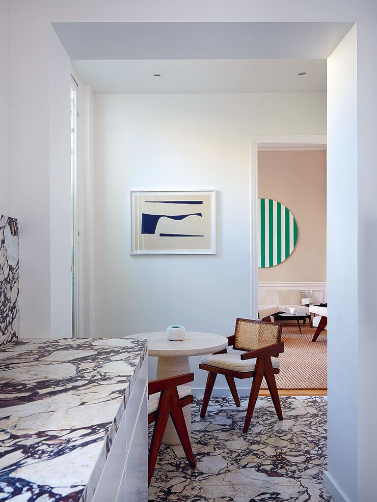 스톤 테이블은 프랑세스코 발자노 제품. 라탄 체어는 피에르 잔느레의 대표작이다.