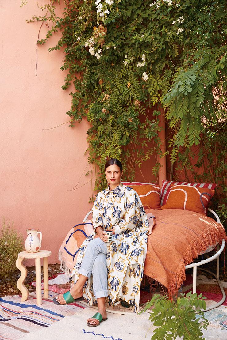 마라케시에 있는 자신의 집 정원에 앉은 디자이너 로렌스 리나에르트. 카펫과 쿠션은 물론 모든 가구와 신고 있는 샌들까지 직접 디자인했다.