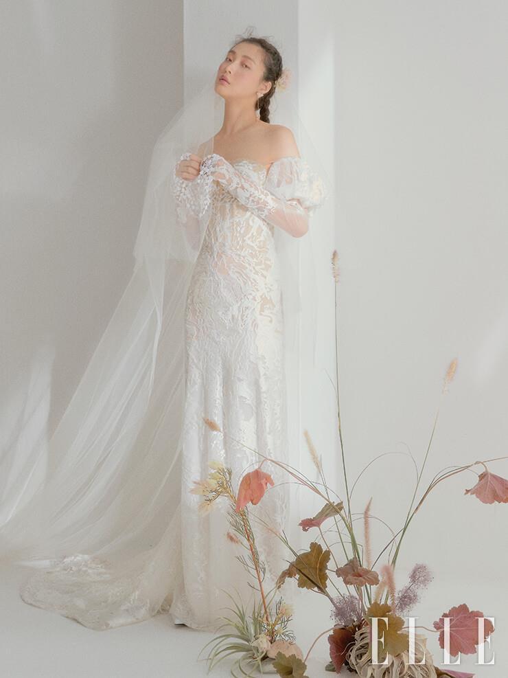 전체적인 실루엣이 고급스러운 레이스 드레스는 Inbal Dror by Atelier Ku. 롱 베일은 Atelier Ku. 이어링은 Atelier Swarovski.
