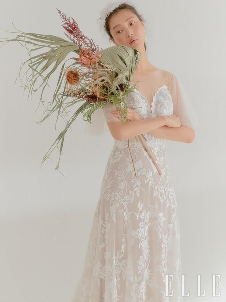 우아함이 돋보이는 레이스 드레스는 Lemere by Novia. 골드 이어링은 Calvin Klein Watches & Jewelry. 헤어 오브제는 The Queen Lounge.