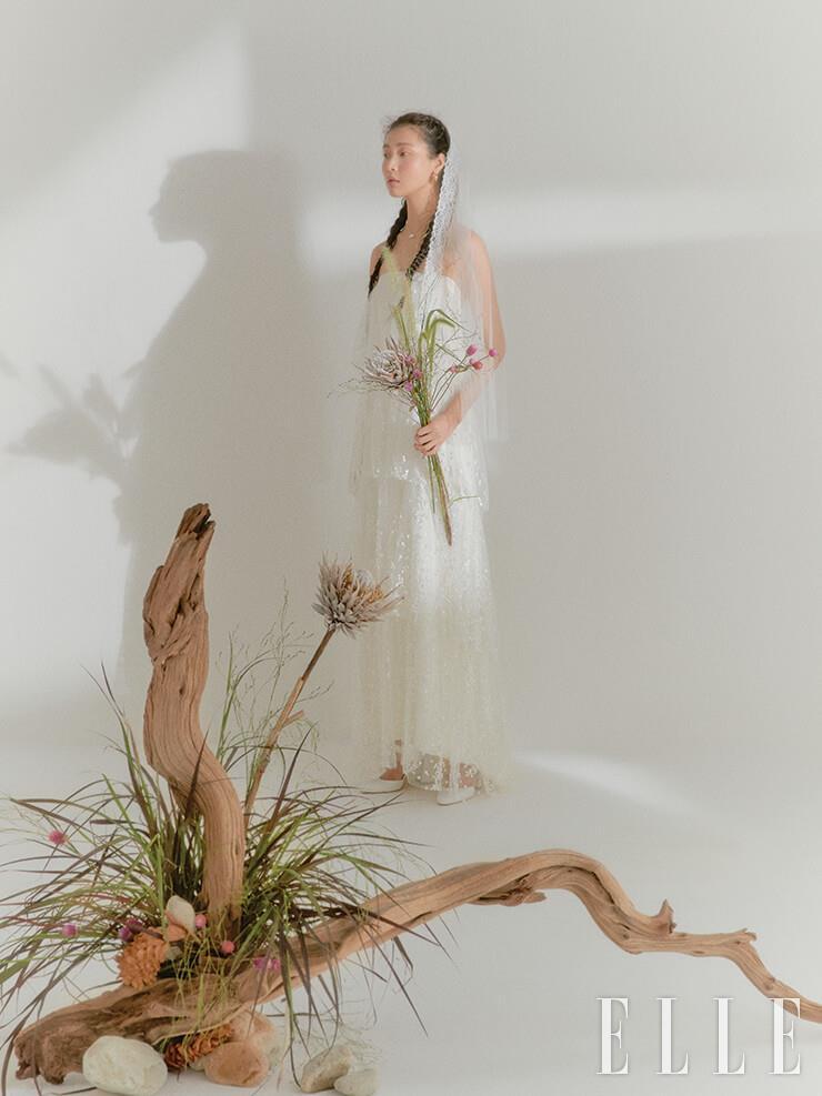 눈이 내린 듯한 티어드 드레스는 Halfpenny London by Soyoo Bridal. 레이스 트리밍 베일은 Abel by K. 골드 이어링과 네크리스는 모두 S_S.il. 슈즈는 Rachel Cox.